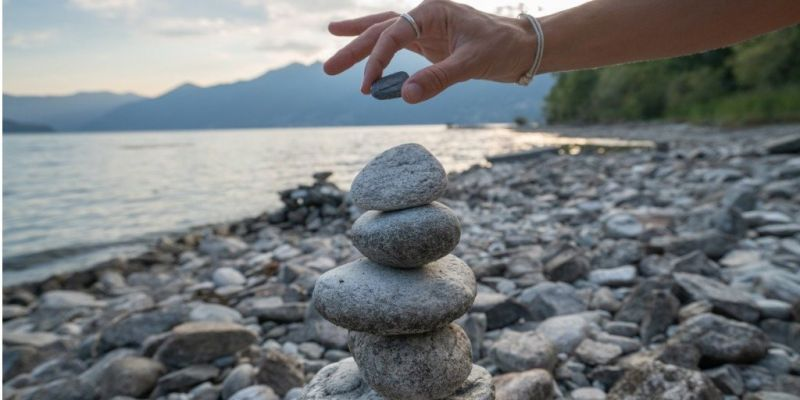 detail-of-person-stacking-rocks-by-the-lake-picture-id1077913420