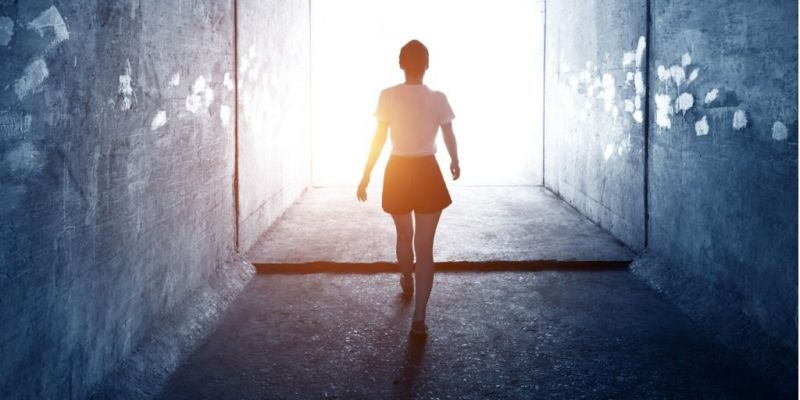 woman-walking-through-a-dark-tunnel-picture-id1177433024