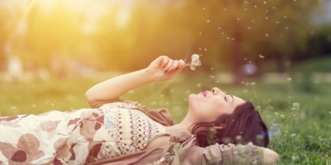 relaxed-woman-in-the-park-blowing-dandelion-picture-id534192686