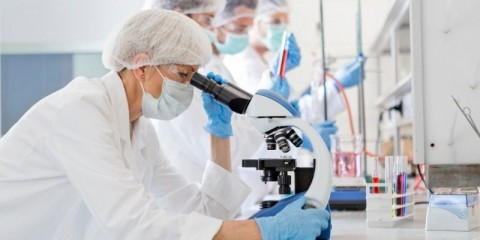 scientists-studying-a-virus-looking-through-microscope-picture-id1215565992