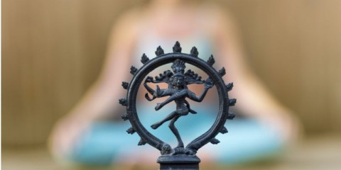 woman-yoga-sitting-lotus-position-with-shiva-goddess-figure-picture-id672950304