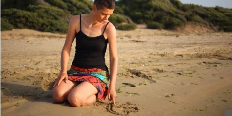 one-woman-with-short-skirt-kneeling-at-the-beach-drawing-a-heart-in-picture-id1212885571