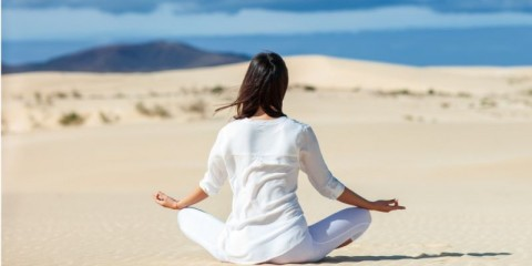 back-view-of-young-woman-meditating-in-lotus-pose-in-desert-picture-id974763392