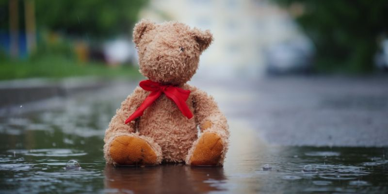 lonely-teddy-bear-sits-in-a-puddle-in-the-rain-picture-id1168703996