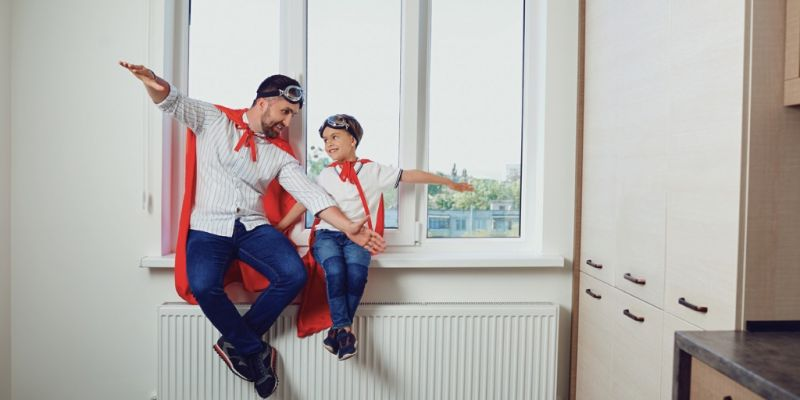 father-and-son-at-the-window-in-the-room-picture-id972155664