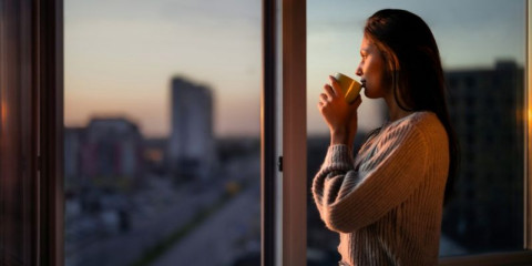 profile-view-of-beautiful-woman-drinking-coffee-by-the-window-picture-id1221311726