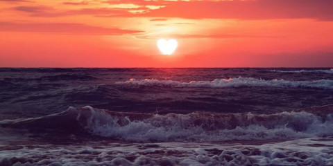 heart-walks-off-into-the-sunset-over-sea-in-dark-clouds-past-love-picture-id1209551870