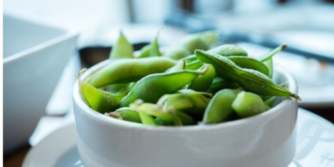 salted-green-edamame-beans-in-white-bowl-picture-id528440208