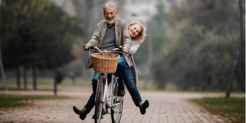 playful-senior-couple-having-fun-on-a-bike-in-autumn-day-picture-id1198993120