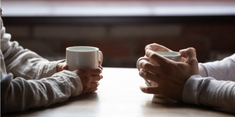 close-up-woman-and-man-holding-cups-of-coffee-on-table-picture-id1152767884