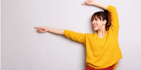 cheerful-young-woman-pointing-finger-against-gray-background-picture-id1045346410